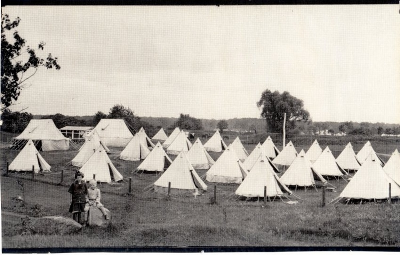 Historic photo of soldiers' teepee style tents at Camp Niagara in Ontario, two children sit on fence in foreground.
