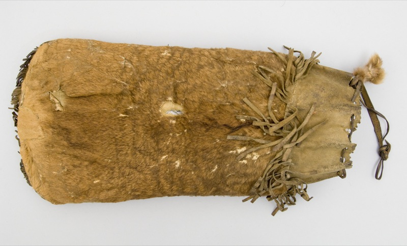 A bag made from fetal or calf moose skin, sewn with sinew and lined with cotton fabric to carry dry meat to eat while travelling.