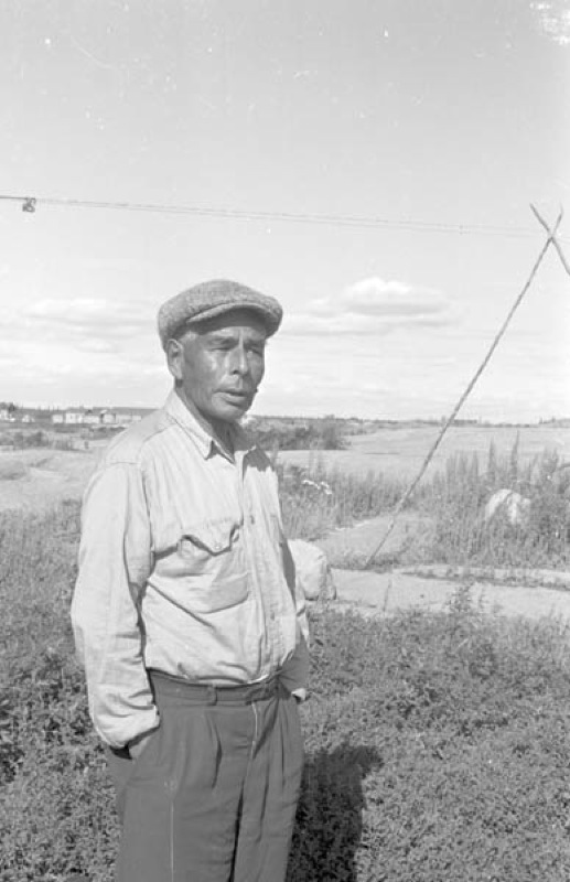 A man stands casually in front of a sprawling northern landscape in Behchoko, Northwest Territories, 1962.