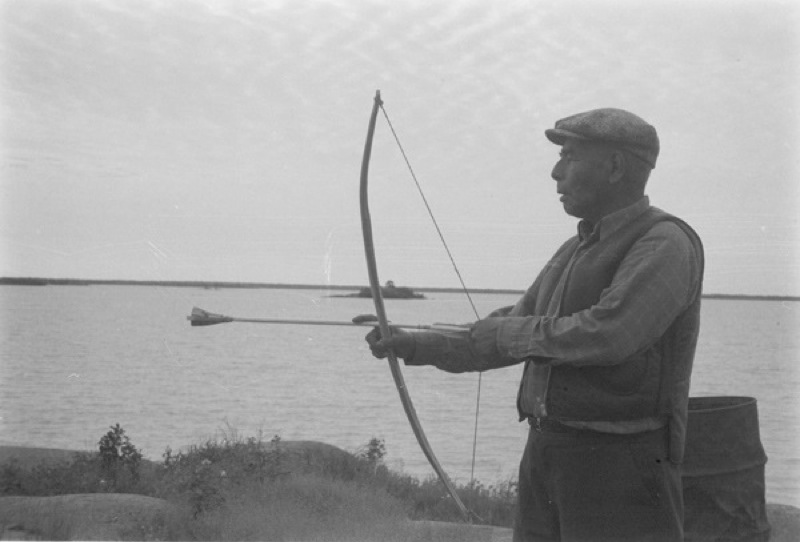 A man photographed practicing with bow and arrows with a large lake background, in Behchoko, Northwest Territories, 1970.