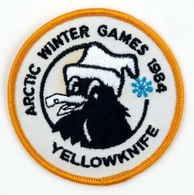 A white badge with the words 'Arctic Winter Games 1984' and a cartoon raven mascot wearing a toque.