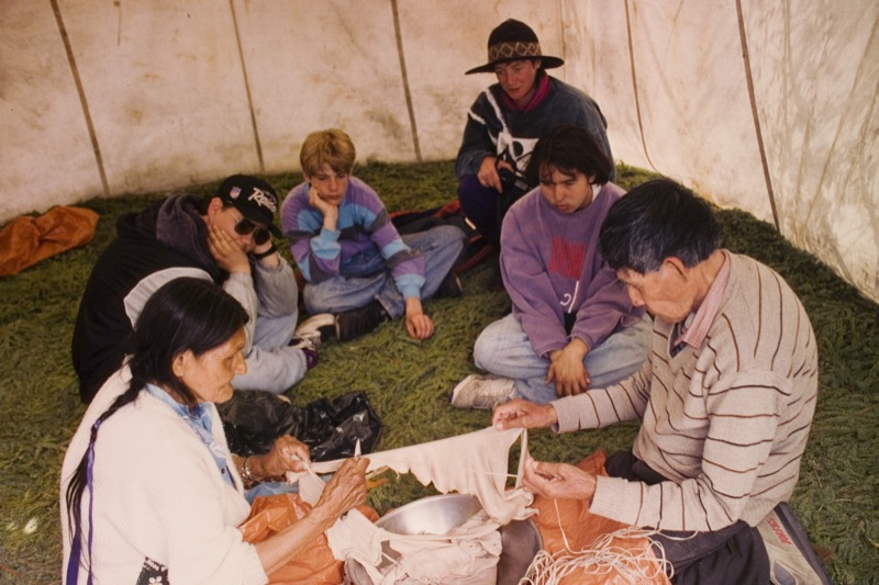 Youth observe as two elders demonstrate traditional methods of cutting babiche inside a Yellowknife shelter.
