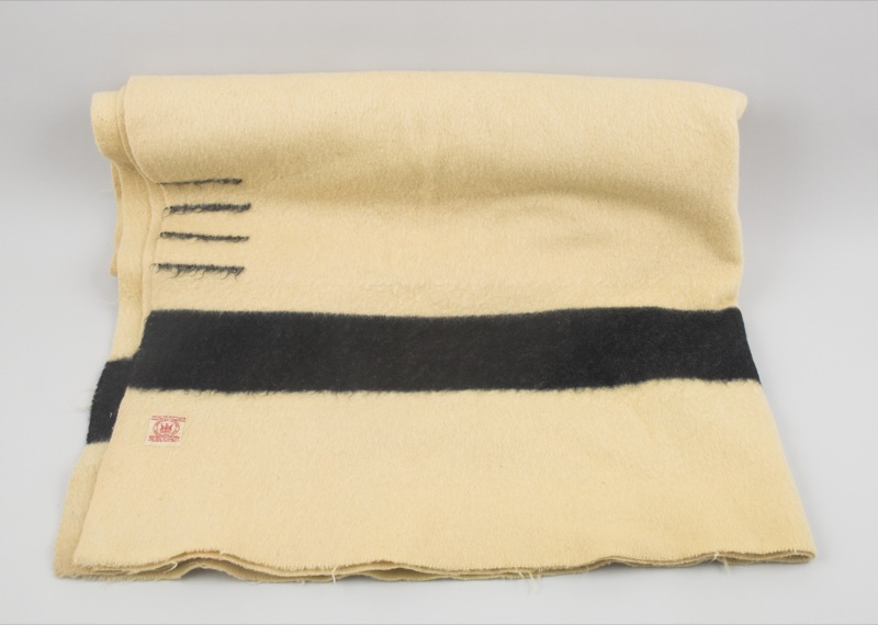 A cream coloured woolen blanket from the Hudson Bay Company with thick back stripe and four parallel lines at one edge, indicating its size.
