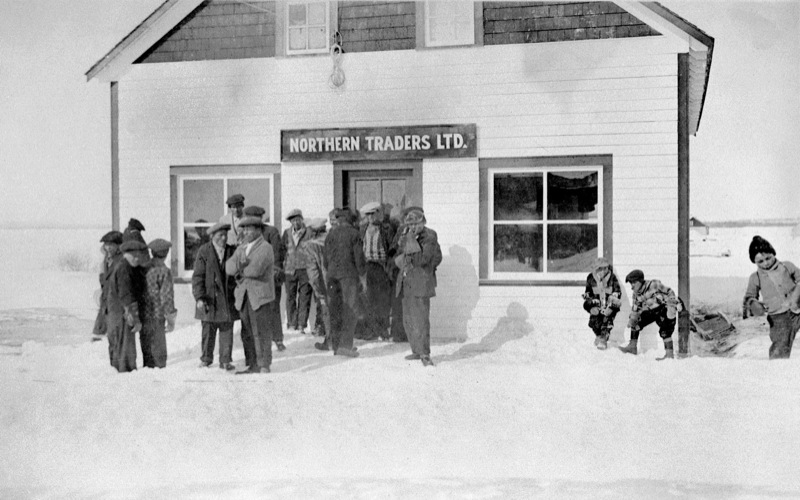 A crowd of men and boys huddle outside a Northern Traders Ltd. store in a snowy landscape, 1930s.