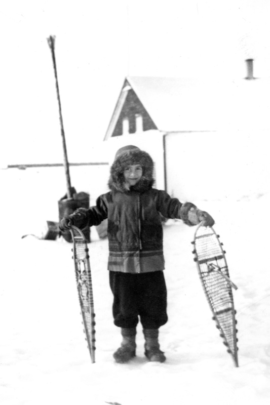 A young girl bundled in a parka holds snowshoes outside a Northern Traders Ltd. store, 1940s.