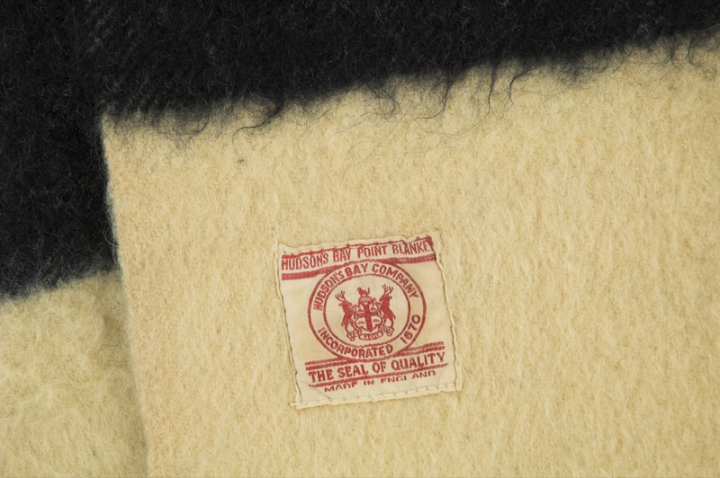 A white label on a cream coloured woolen blanket identifies it as a high quality Hudson's Bay point blanket.