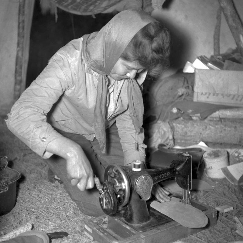 A woman stitching moccasins on a Singer sewing machine at Colville Lake, Northwest Territories, 1963.