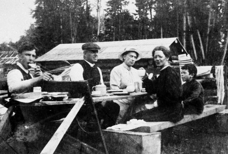The Tremain family seated at a makeshift table, wood cabin in background at Fort Simpson, 1919.