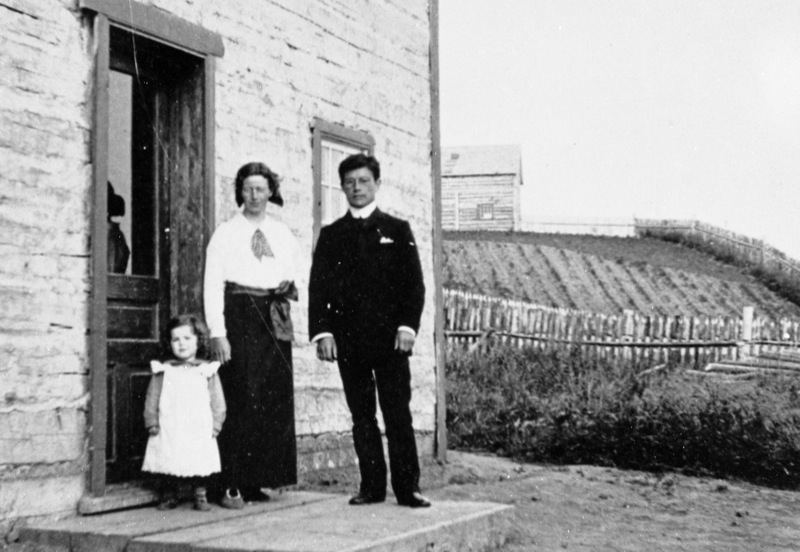 A man, woman and girl pose on the stoop of a wooden home, rolling fields in background. Fort Norman, 1915.