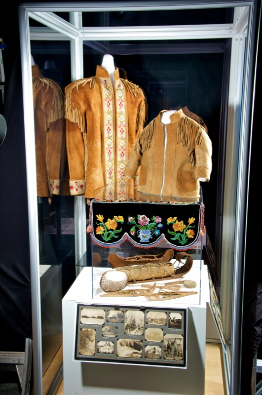 A museum display consisting of beaded moose hide jackets, moccasins, belts, models, and a shelf valance.