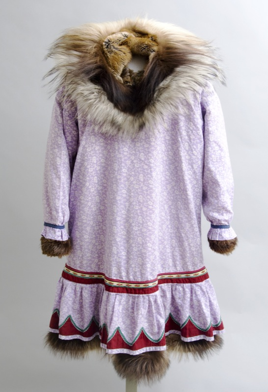 Decorative pink cotton fabric covers this large parka made from over 100 brown muskrat furs, with a ruff made from wolf and wolverine furs.