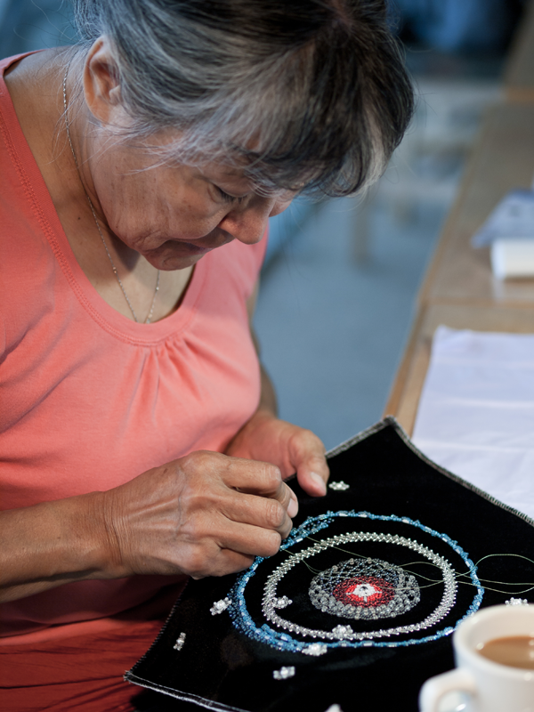 Artist Margaret Nazon working on a colourful textile artwork inspired by deep space images, 2012.