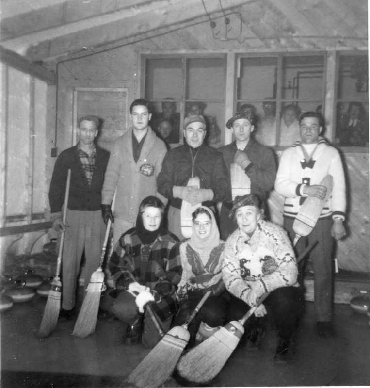 Posed portrait of the men and women of the Giant Curling Club, Yellowknife, 1950s, inside their small club.