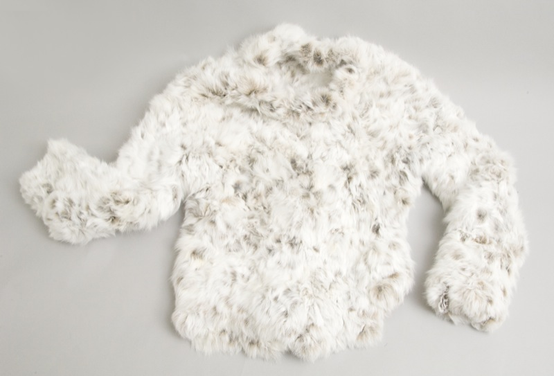A white hoodless jacket made from the pelts of snowshoe hares. It takes about 30 rabbit hides to make this kind and size of jacket.