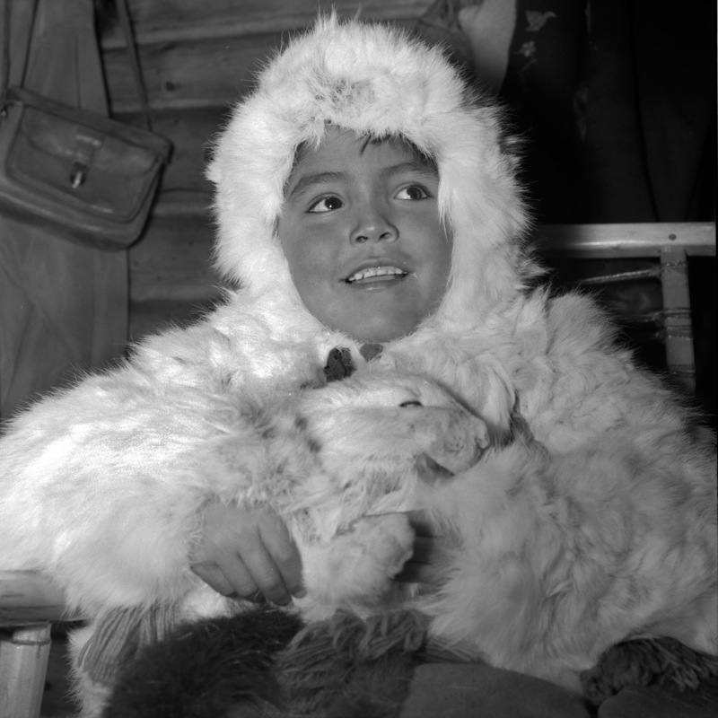 A smiling young boy dressed in a white hare-skin parka holds a rabbit, at Colville Lake, 1969.