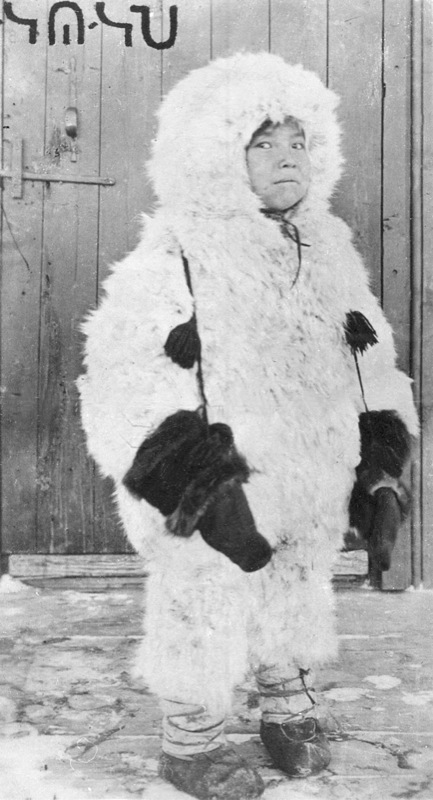 A Dene girl stands in snow wearing a hare-skin outfit with enormous hood, Tulita, Northwest Territories, 1921.