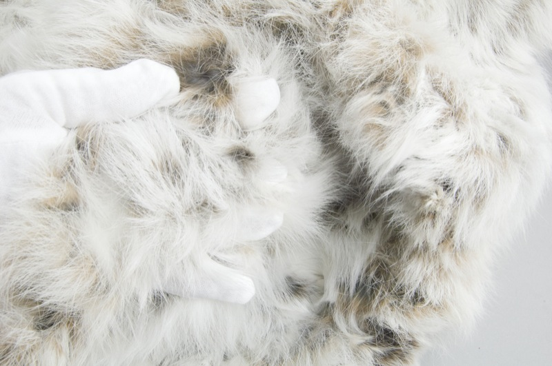 A gloved hand holds the snowshoe hare pelt jacket open to show the open mesh and light brown hews of the fur.
