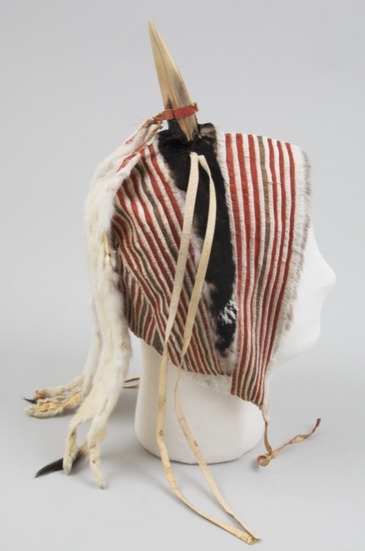 A bonnet-style dance hat made with narrow strips of sealskin alternating with skin dyed red. A loon's beak stands up from the top of the hat.