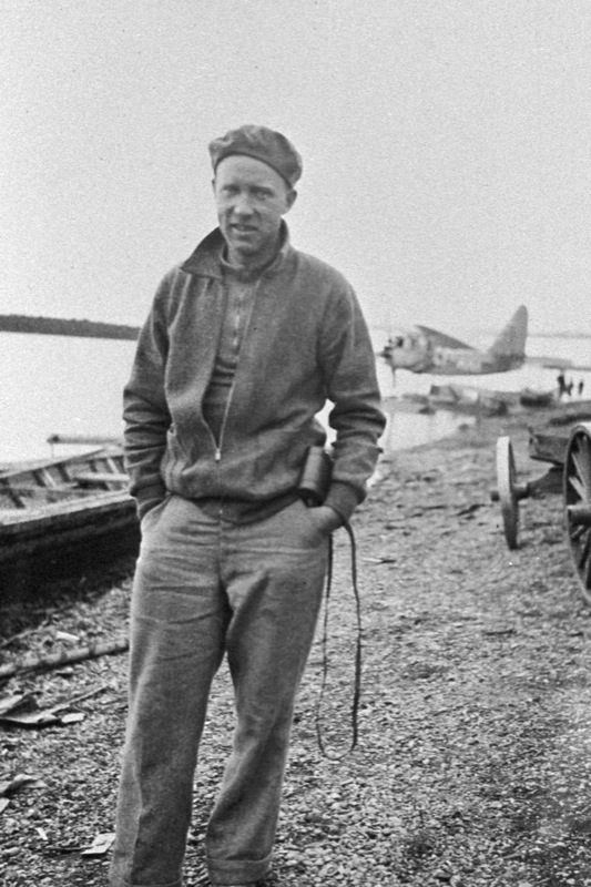 A man poses on a barren shore in northern Canada, 1920s–30s. His plane floats at a dock in the background.