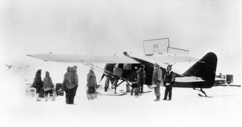 Ten Royal Canadian Mounted Police and civilian personnel stand talking near a bush plane in a snowy open landscape, 1932.