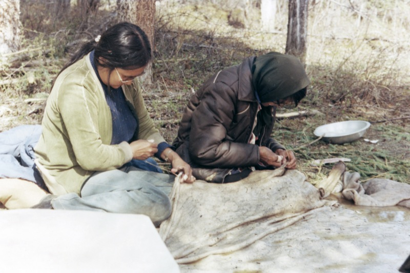Two women seated on ground sewing large pale moose skins, together during making of the boat.