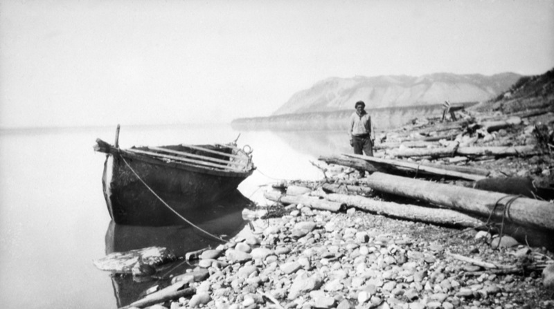 Man stands beside a large moose skin boat floating on the shore of the Mackenzie River, Northwest Territories.