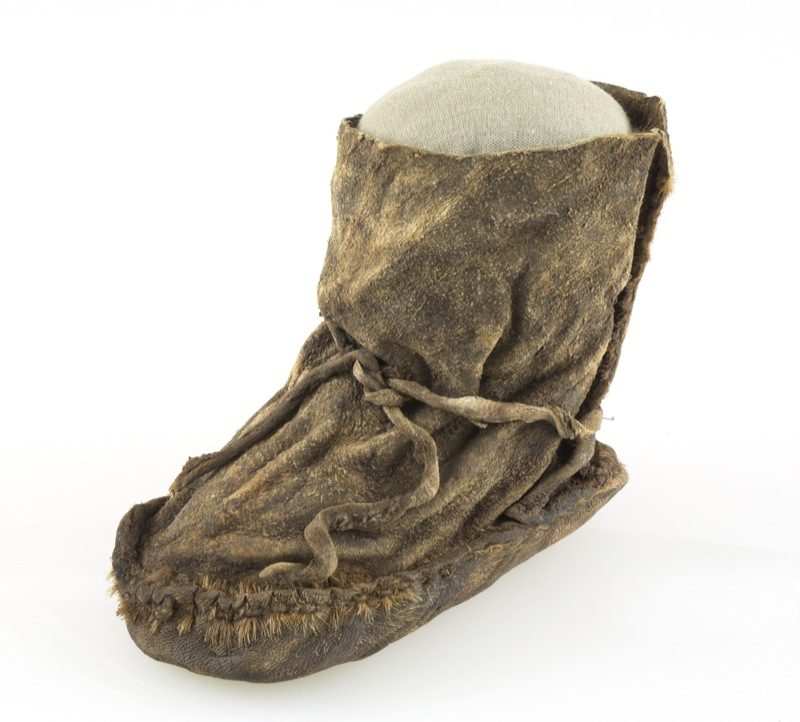 An aged Palaeolithic sealskin shoe retaining the basic shape of a human foot and featuring two strips of sealskin as laces.