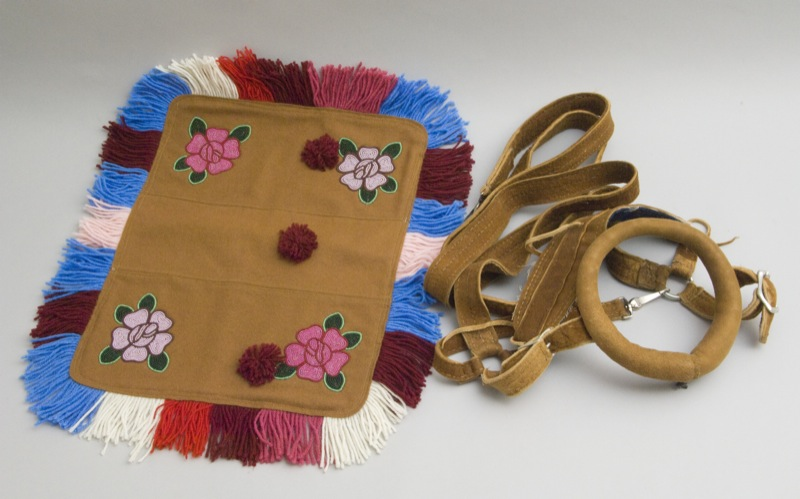 A smoked moose hide dog harness and blanket of coarse wool cloth with canvas backing, decorated with yarn pompoms and beaded flowers.
