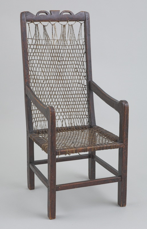 A small wooden children's chair with a netted seat of untanned hide, probably caribou in this case, cut into narrow strips.