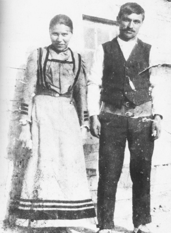 A young man and woman, Celine and Joseph Bouvier, pose outside a wooden building, circa 1912.