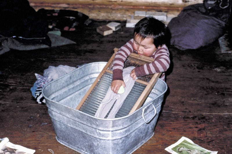 A very young boy using a scrubbing board to do laundry at Sans Sault Rapids on the Mackenzie River, 1979.