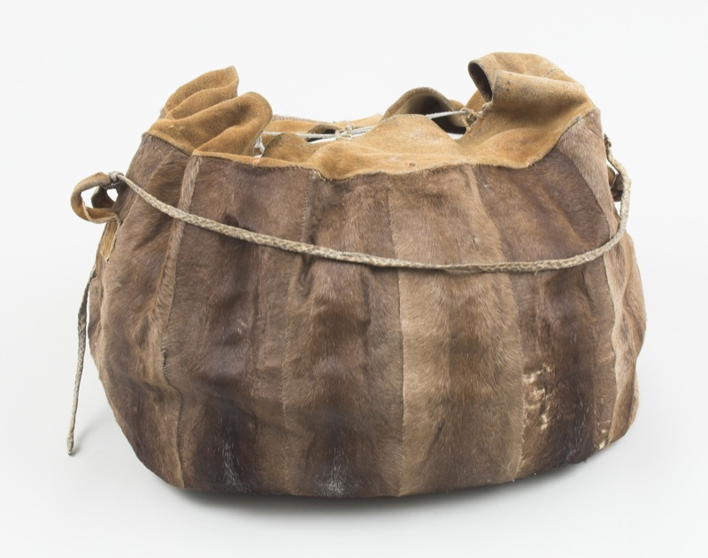 A small bag made using caribou leg skins sewn together with fine sinew stitches with a drawstring at the mouth, used to carry sinew on trips.
