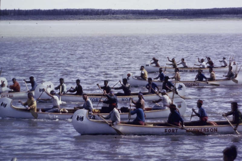 Six canoes full of paddlers paddle vigorously during the 1970 Northwest Territories Centennial race.