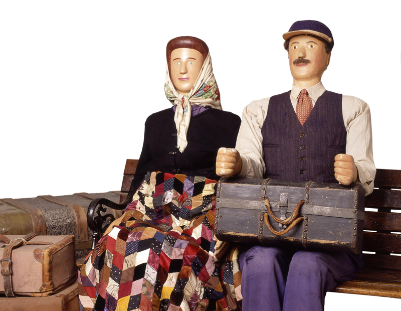 Life sized carved figures featuring a man and woman seated on a bench in early 20th century dress, surrounded by suitcases.