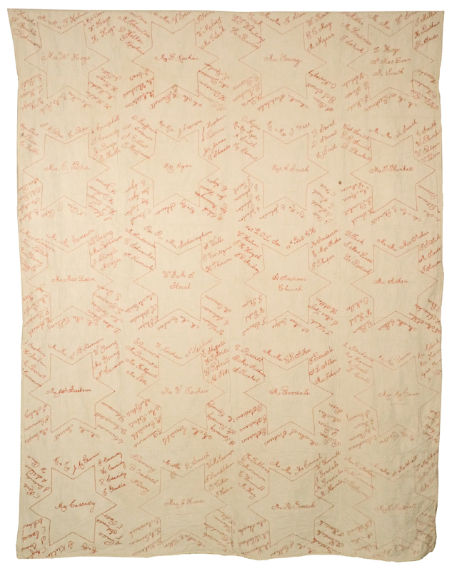 A large rectangular quilt featuring many red sewn six pointed stars surrounded by many signatures on a beige background.