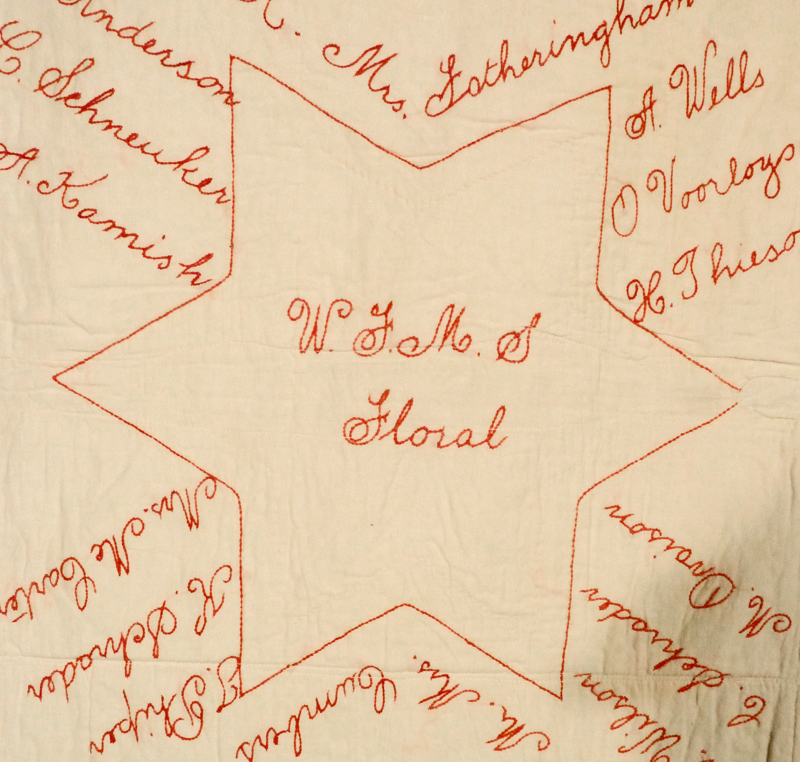 A detail of a quilt square, a red sewn six pointed star surrounded by signatures on a beige background.