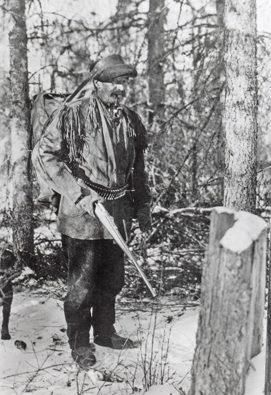A candid photo of an older, bearded Klaus Epp hunting in the buckskin suit in a snowy forest setting.
