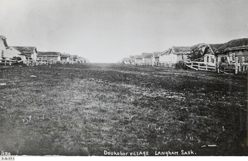 Historic photo of a Doukhobor communal village, with a broad central grass road.