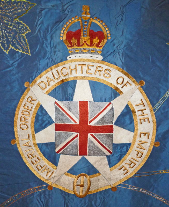 Close up of the Imperial Order Daughters of the Empire crest featuring the British flag on the blue wall hanging.