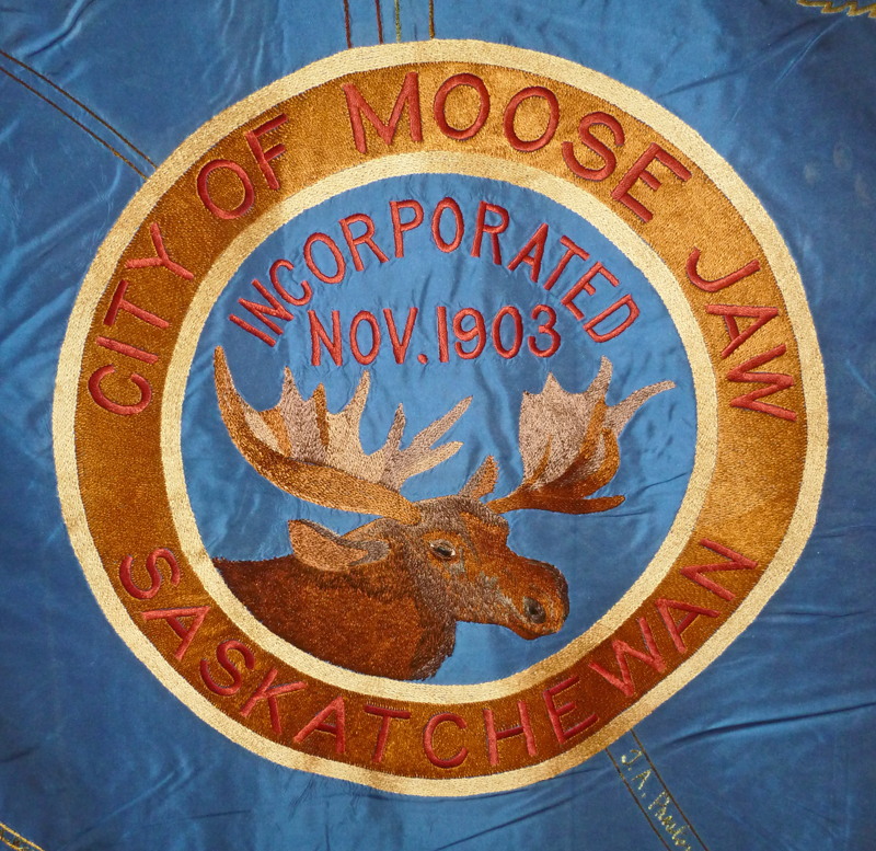 Close up of the Moose Jaw, Saskatchewan crest featuring a brown moose on the blue Imperial Order Daughters of the Empire wall hanging.