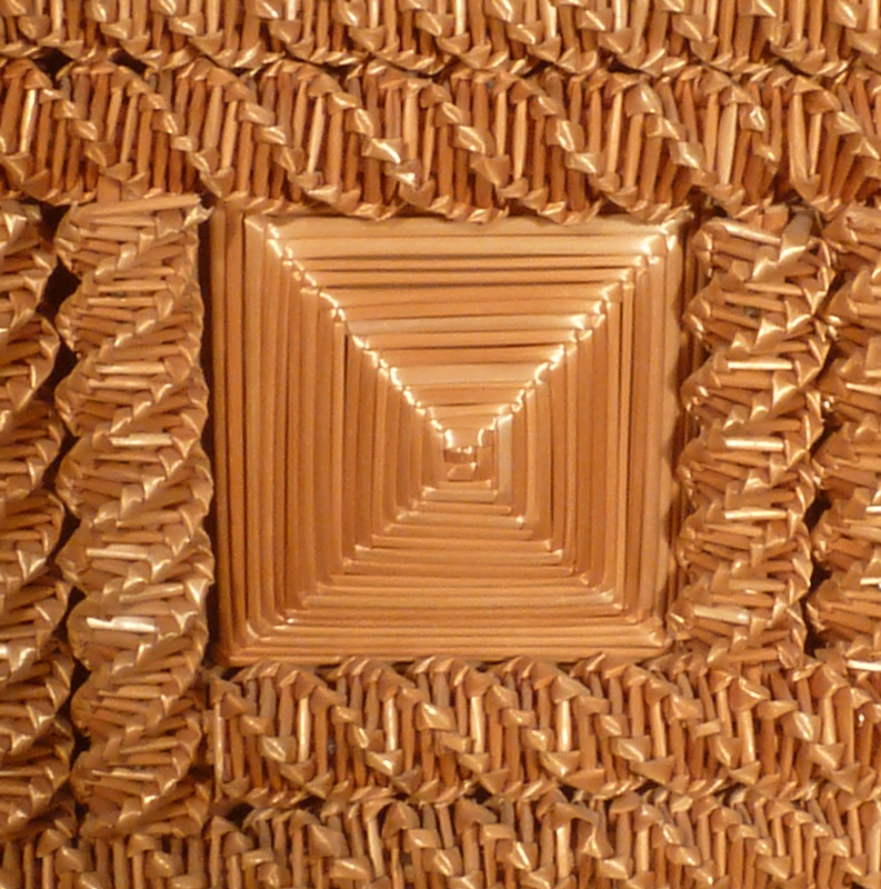 Close-up view of detailed oat straw weaving in a plant stand made by Adam Reinhold.