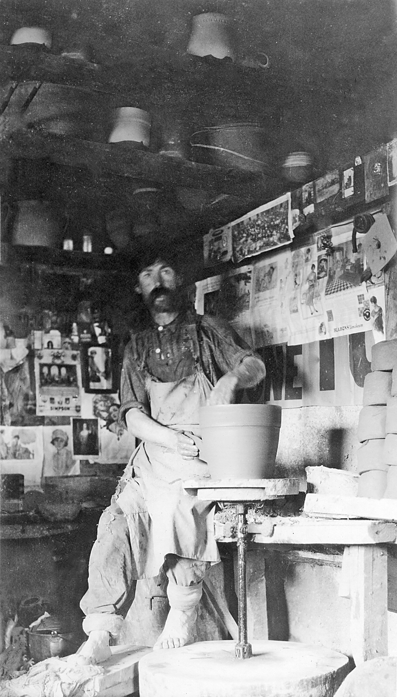 Peter Rupchan at a pottery wheel in his workshop, partially finished and broken pottery surrounding him.