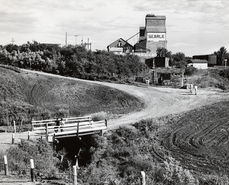 A winding dirt road leads to the Searle Grain Company elevator in this rural scene, 1955.