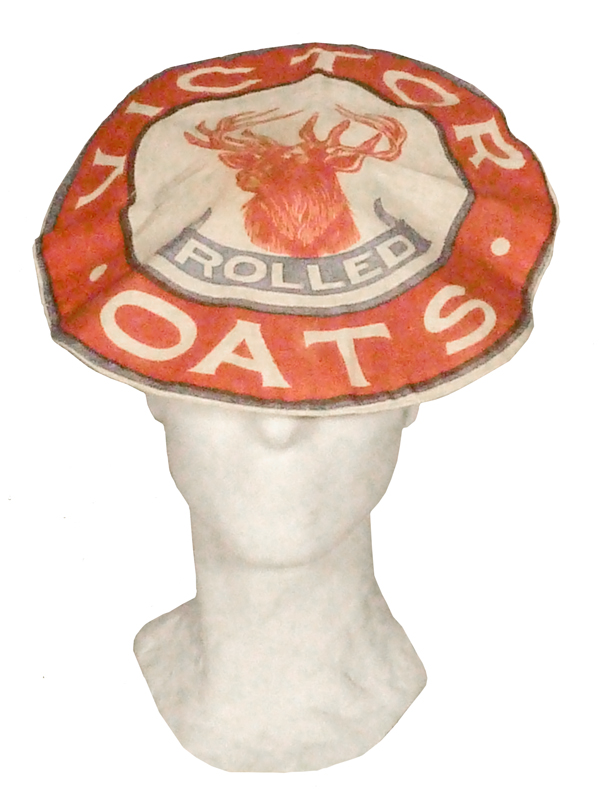 Red hat made from a Victor Rolled Oats bag, with prominent accompanying label.