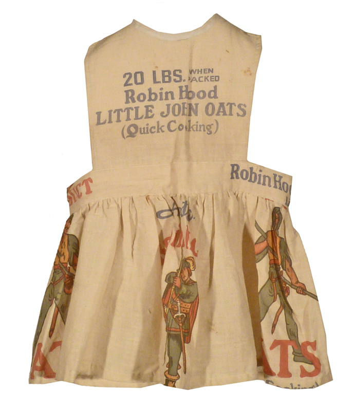 Child's pinafore made from sacking prominently covered in Robin Hood oats company labels.
