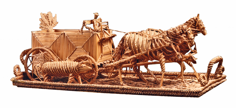 A wheat straw sculpture of a horse drawn wagon with rider, a large pig walking beside it.