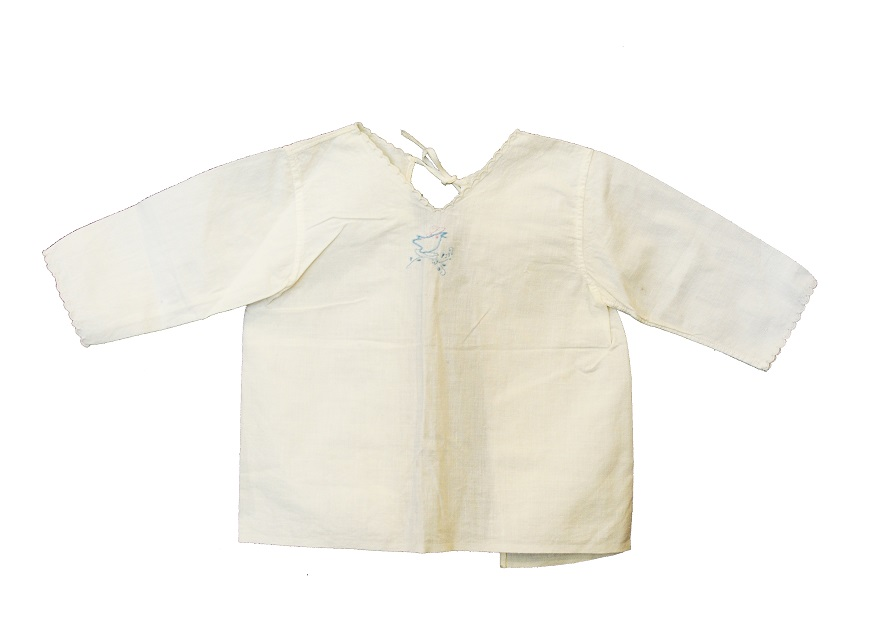 An off-white shirt displayed flat against a white background. The shirt has three-quarter sleeves, scalloped edging at the sleeve cuffs and neckline, and the embroidered outline of a small blue bird with a pink hat sitting on a floral spring centered just below the neckline.