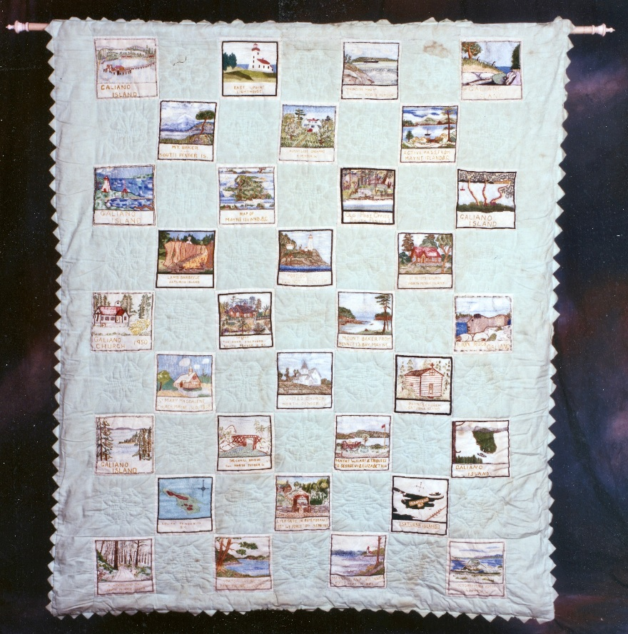A light-blue quilt with 32 appliqued patches embroidered with images and names of landscapes, building and maps.