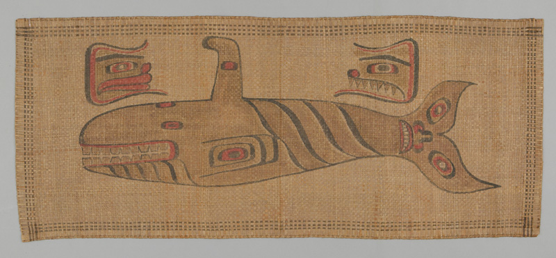Cedar mat featuring a side view of a large stylized red and black whale with a face on its tail, flanked by two wolf heads, one bearing sharp teeth.