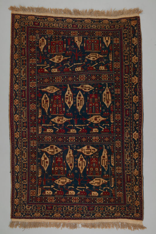 A large fringed rug of dark reds and blues, featuring stylized depictions of weapons, battles, and destruction reflecting conflict in Afghanistan.
